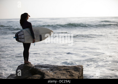 Young woman standing on rocks with surfboard - Stock Photo