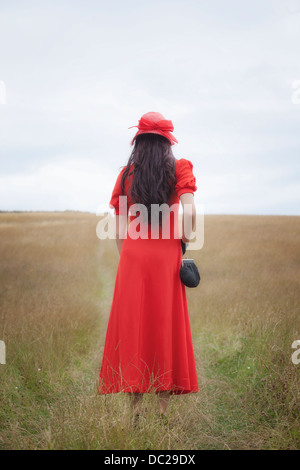 a woman in a red dress is walking over a field - Stock Photo