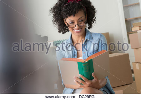 Mid adult woman reading book surrounded by cardboard boxes - Stock Photo
