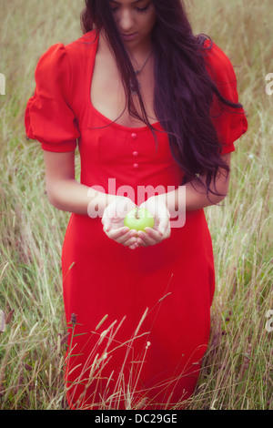 a woman in a red dress, holding a green apple - Stock Photo