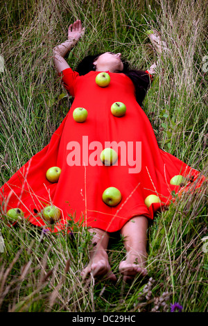 a woman in a red dress, lying in the grass with green apples on her dress - Stock Photo