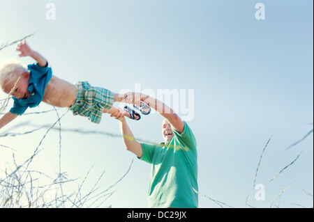 Father spinning son in field, low angle - Stock Photo