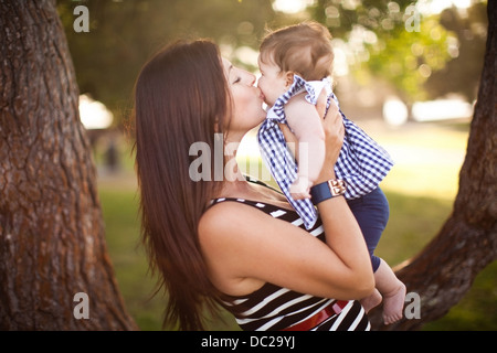 Portrait of mother kissing baby daughter - Stock Photo