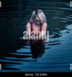 a woman in a red dress is swimming in a lake - Stock Photo