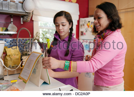 Mother and daughter reading recipe - Stock Photo