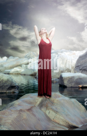 a woman in a red dress is standing on a rock in the water and enjoying the sun - Stock Photo