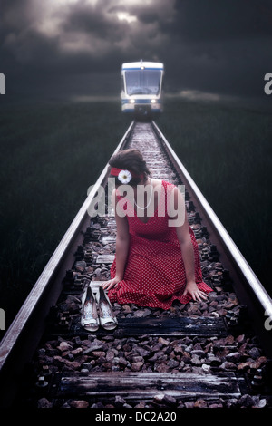 a girl in a red dress is sitting on railway tracks while a train is coming - Stock Photo