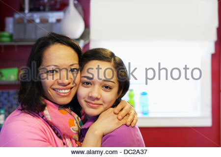 Portrait of mother hugging daughter in kitchen - Stock Photo