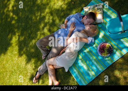 Young couple kissing on picnic blanket, overhead view - Stock Photo
