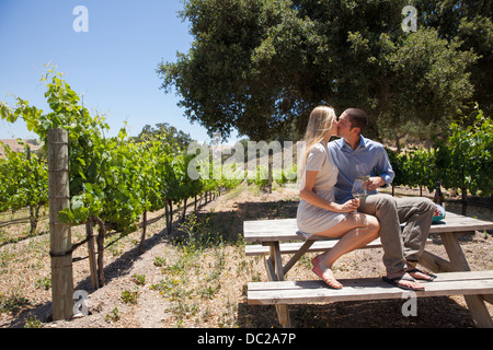 Young couple kissing on picnic table in vineyard - Stock Photo
