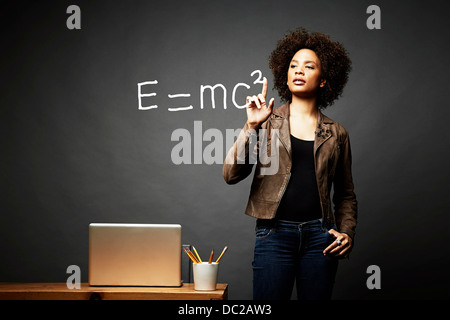 Woman solving mathematical equation - Stock Photo