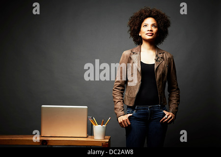 Woman with hands in pocket looking upward - Stock Photo