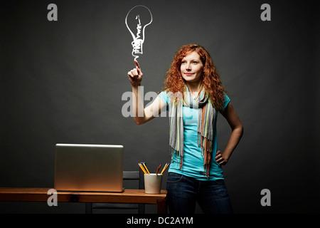 Woman drawing a light bulb - Stock Photo