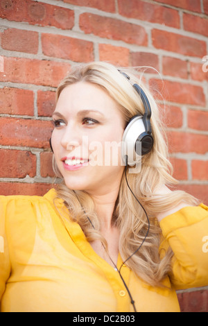 Close up of woman with headphones against brickwall - Stock Photo
