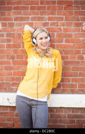 Woman wearing headphones standing against brickwall Stock Photo