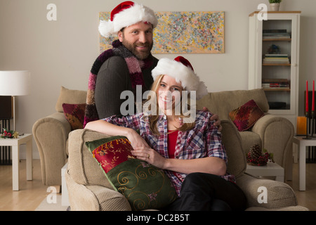 Husband and wife in Santa hat looking at camera - Stock Photo