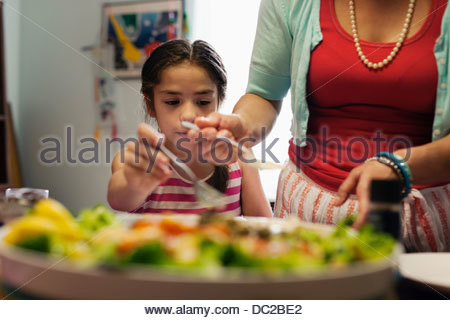 Mother serving food to daughter - Stock Photo