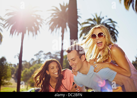 Man and women playing piggy back - Stock Photo