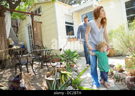 Parents & child walking in the backyard - Stock Photo