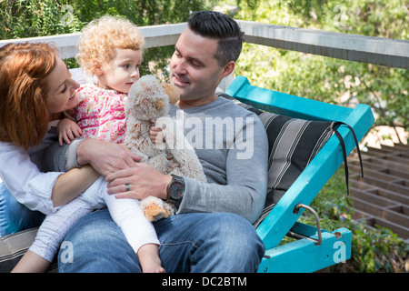 Couple on deckchair with child - Stock Photo