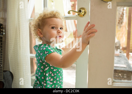 Toddler opening door - Stock Photo