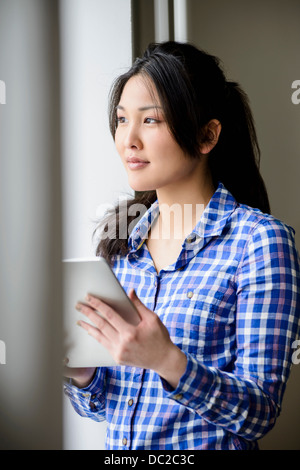 Woman with digital tablet looking into distance - Stock Photo