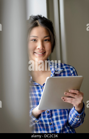 Woman with digital tablet looking at camera - Stock Photo