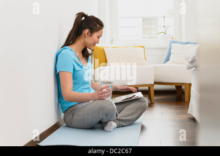 Woman sitting on mat using digital tablet - Stock Photo