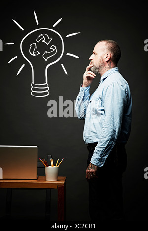Man contemplating on recycling idea - Stock Photo