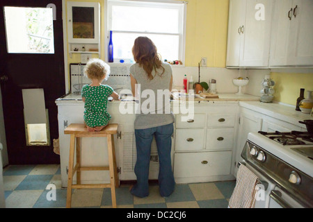 Mother and child at kitchen sink - Stock Photo