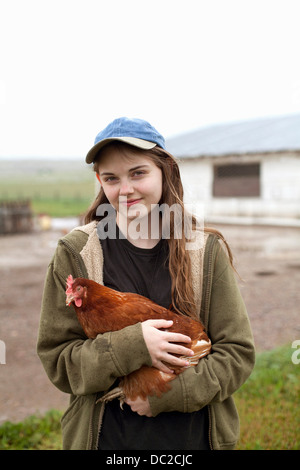 Girl carrying hen - Stock Photo