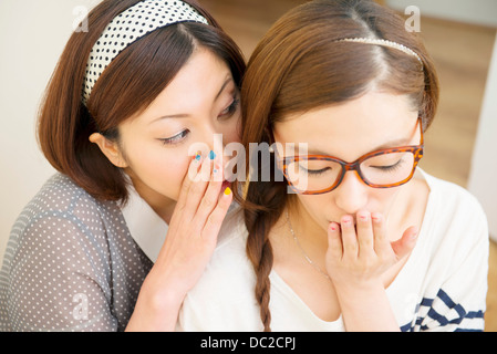 Woman whispering to friend - Stock Photo