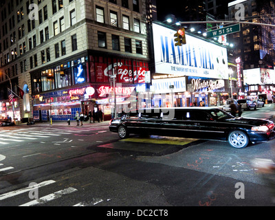 night view bright lights of Broadway with pedestrians & long sleek stretch limousine crossing Broadway intersection - Stock Photo