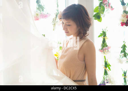 Woman lifting curtains of glass windows with dangling flowers - Stock Photo