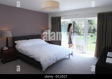 Woman looking through glass door of bedroom - Stock Photo
