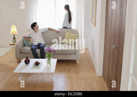 Husband turning round on sofa to look at wife - Stock Photo