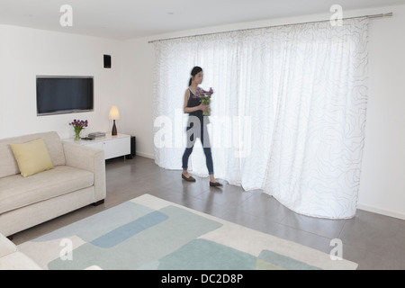 Woman with vase of flowers walking past curtains - Stock Photo