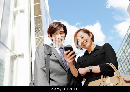 Business man and woman looking at message on smartphone - Stock Photo