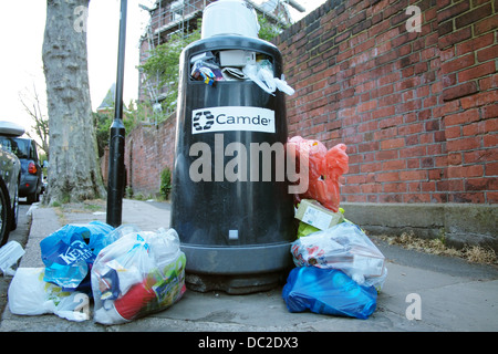 Overflowing rubbish bins on a residential street in London UK - Stock Photo