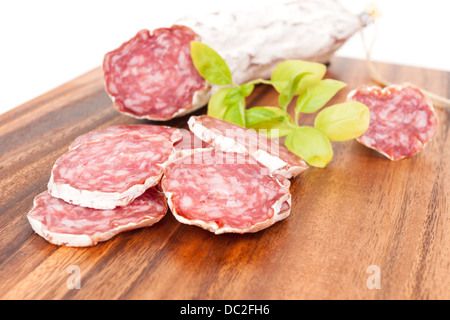 sliced salami on white background with basil leaves - Stock Photo