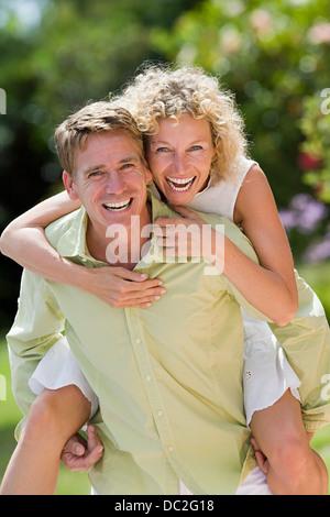 A man giving a woman a piggy back - Stock Photo