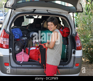 Guy puts the bag in the luggage of the car during the departure for the summer holidays - Stock Photo