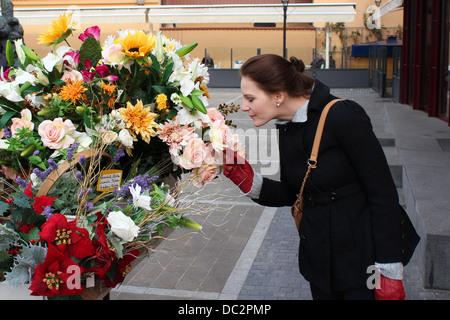 Woman smelling flower at market - Stock Photo