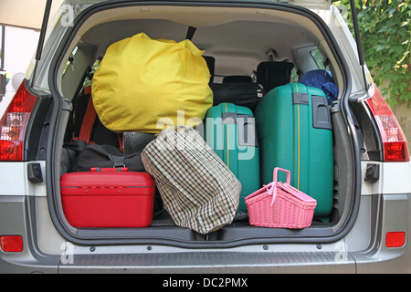 two green suitcases and many bags in the trunk of the car ready to depart for the holidays - Stock Photo