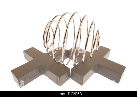 Iron wire tangled up into spiral ball resulting in a shiny chrome sphere, lying on its side on top of two gray crosses - Stock Photo
