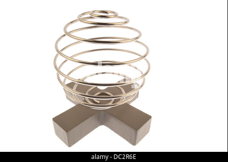 Iron wire tangled up into a spiral ball resulting in a shiny chrome sphere and standing on top of a gray cross and - Stock Photo