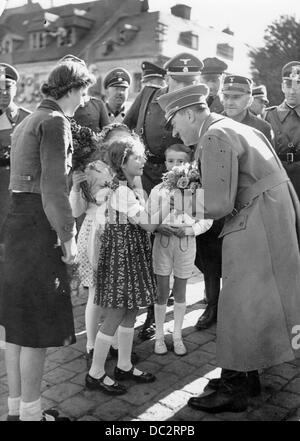 The image from the Nazi Propaganda! shows Adolf Hitler as girls give him flowers. Date and place unknown (around - Stock Photo