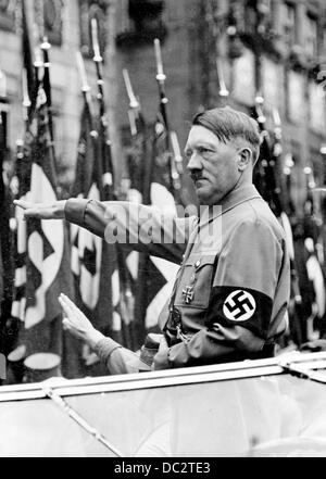 The Nazi Propaganda! image shows Adolf Hitler saluting members of the SA, SS, NSKK, and NSFK, which march past him - Stock Photo