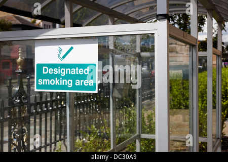 designated smoking area shelter outside an office building in the UK - Stock Photo