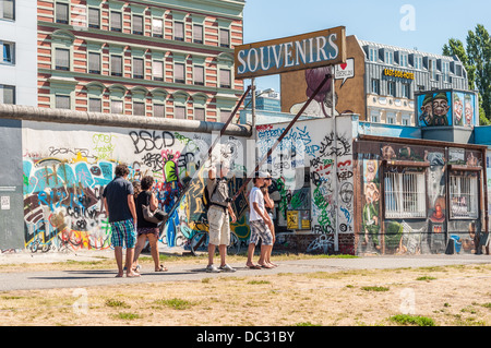 People at the Berlin Wall, East Side Gallery, souvenirs shop with graffiti - Berlin Germany - Stock Photo